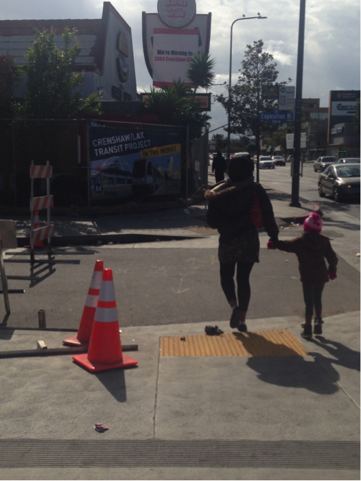 South Los Angeles residents walk pass the construction site for the Crenshaw/LAX line on Crenshaw and Exposition Boulevards. A new labor agreement between the union and contractors could lead to more jobs for residents in the coming years. | Jordyn Holman