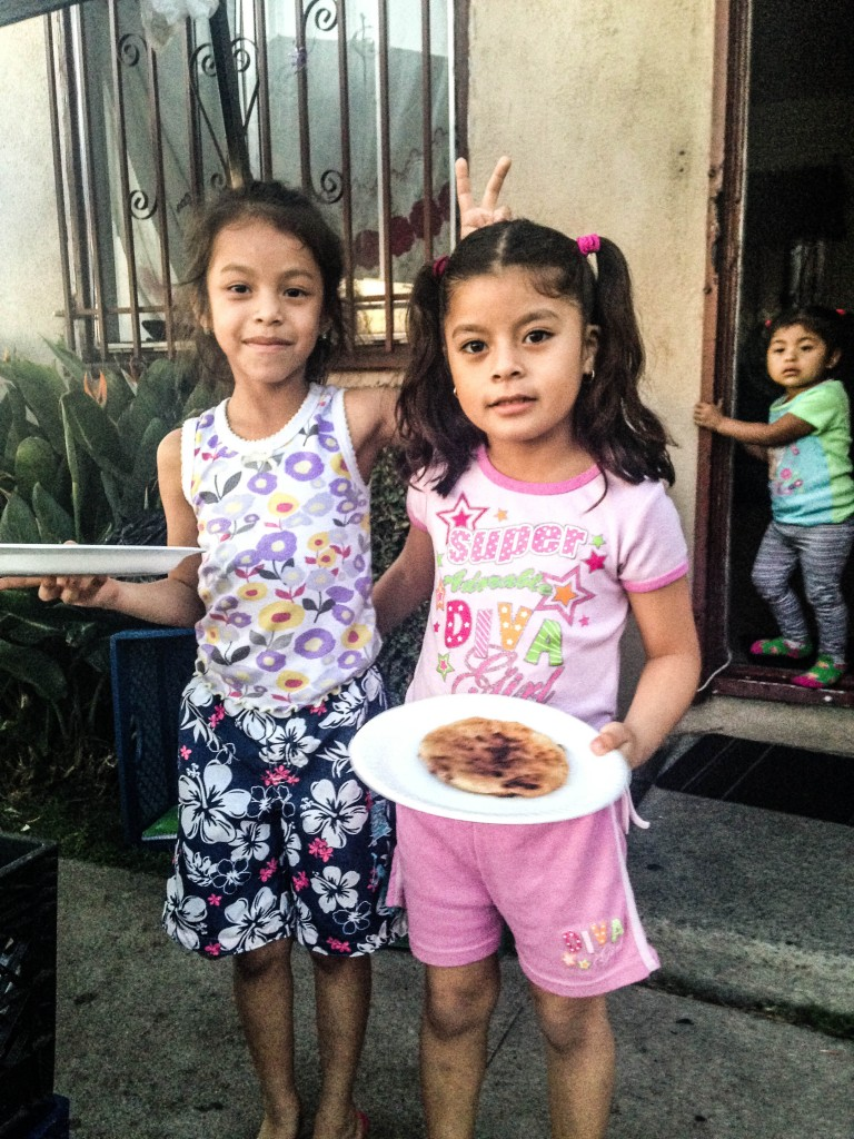 Girls stand outside their house in South LA where their family cooks and sells pupusas at an outdoor stand. | Daina Beth Solomon