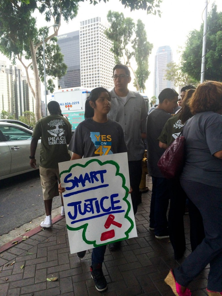 "A student pushes for Proposition 47 with a sign reading ""Smart Jusice."" 