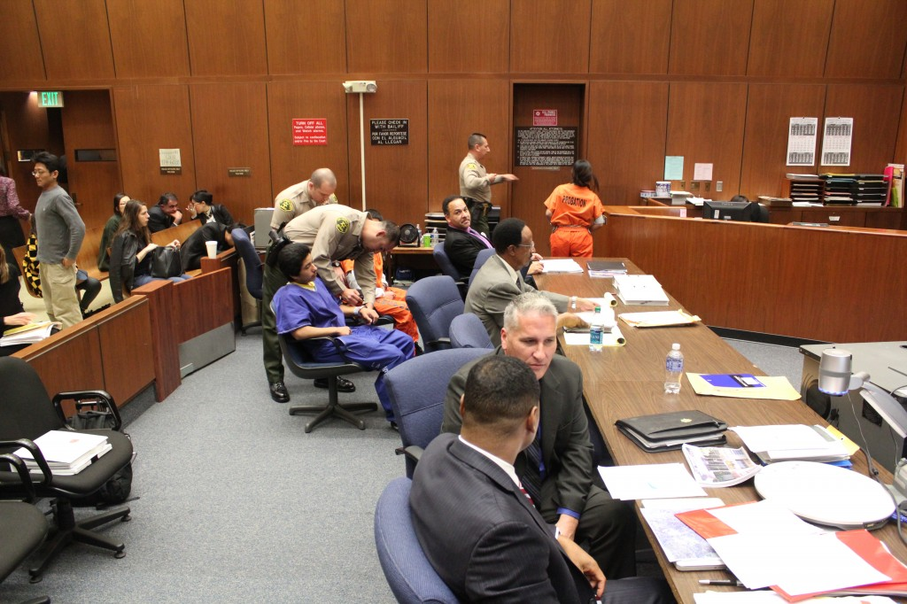 Alejandra Guerrero, in orange, is escorted out of the courtroom during a recess. Bailiffs prepare Alberto Ochoa, also in orange, along with Jonathan DelCarmen, in blue, to follow. | Daina Beth Solomon