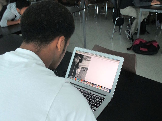 A student browses a historic photo album from the Watts Riots. | Photo by Anna-Cat Brigida