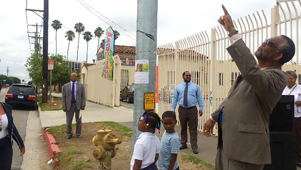 Councilman Curren Price looks up at the new traffic signal on the corner of Figueroa Avenue and 56th Street.