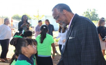 Council member Curren Price speaks with a student at West Vernon Elementary School at the launch of their grant bid.