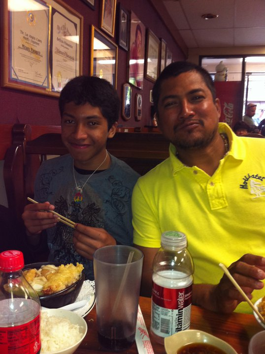 A younger Miguel with his father at a restaurant in Los Angeles.