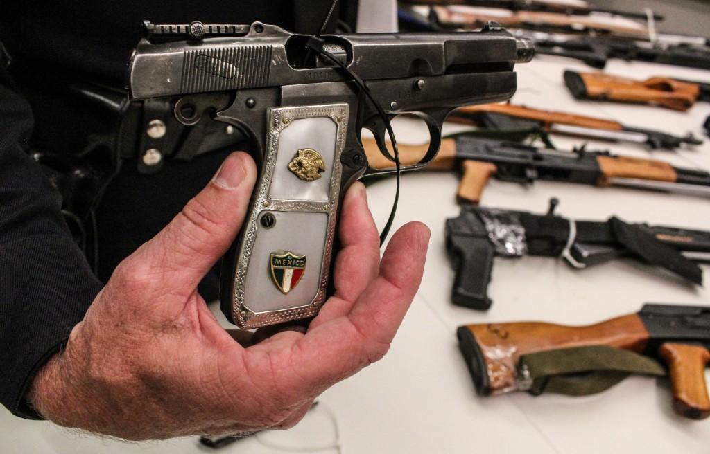 Commander Andrew Smith holds a 9mm handgun. | Daina Beth Solomon