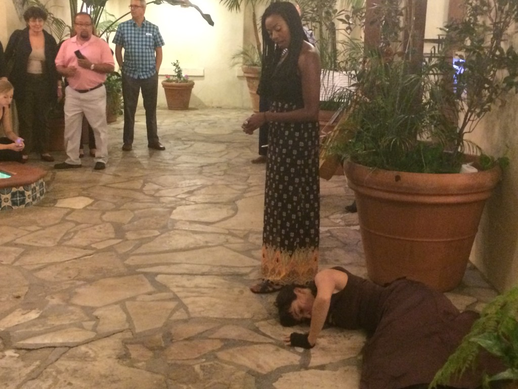 "Singer Tatiana Williams sings lyrics to Paul Lawrence Dunbar's poem ""Sympathy,"" while dancer Teresa Barcelo performs in the courtyard of Dunbar Village. | Christina Campodonico"