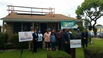A neighborhood pastor speaks at Pinkney's solar panel installation.